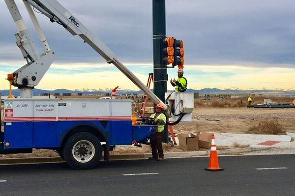 Streets staff installing traffic light